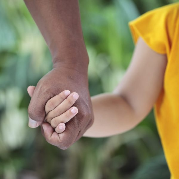 An adult holding the hand of a child