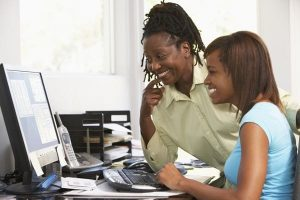 African American mom & teen looking at computer