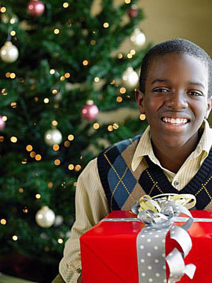 Older Boy holding present next to Christmas Tree