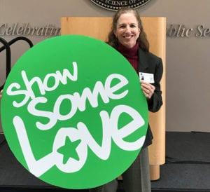 Tamara Arsenault, Development Director holding Show Some Love big green circle sign