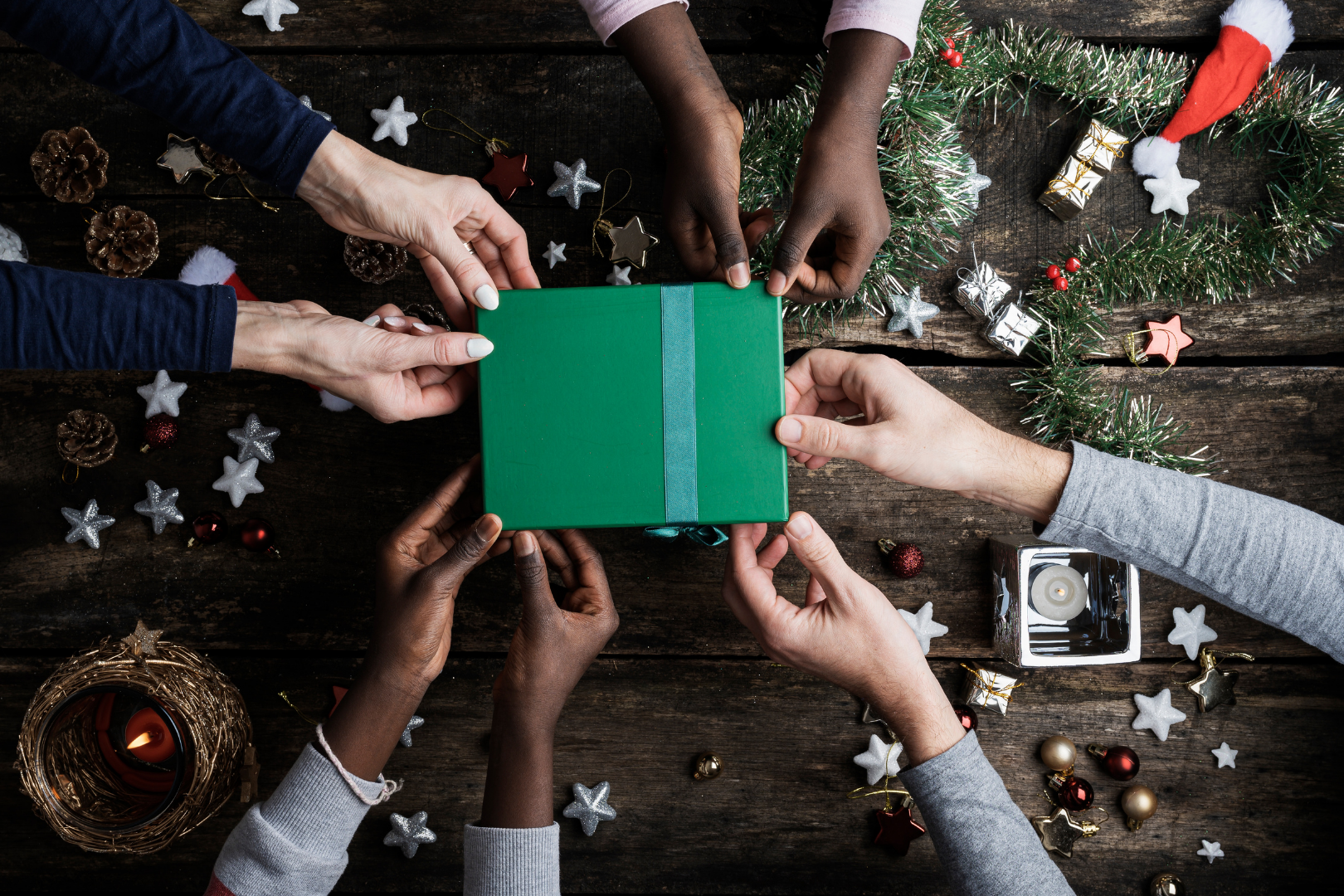 Multi cultural hands holding a present with holiday theme wooden background