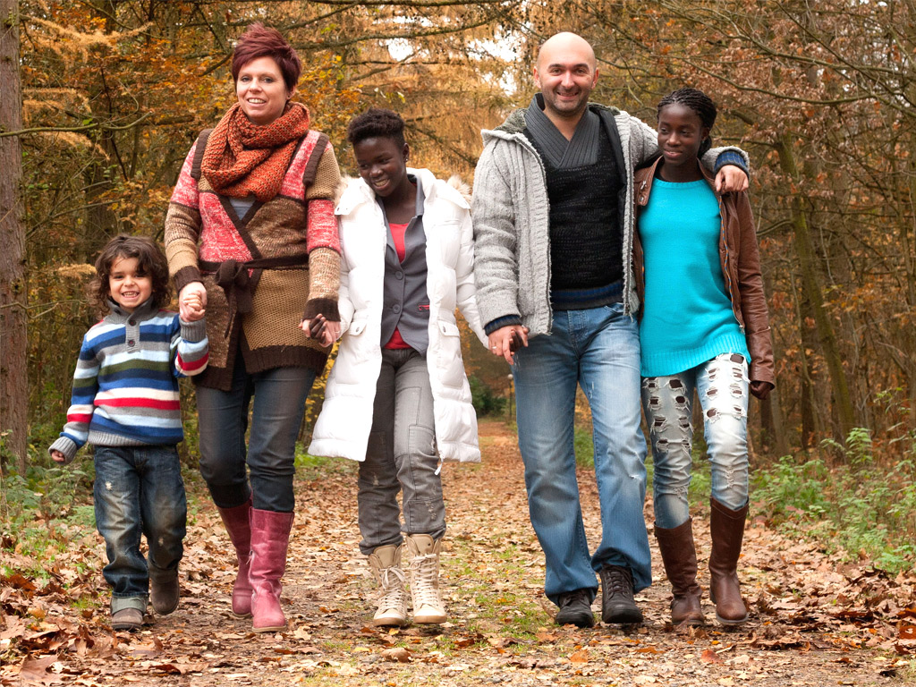 Transracial Family Holding Hands Walking Together in Fall Scene