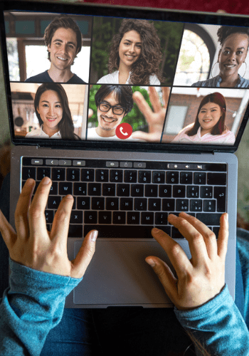 Someone typing on computer with people on computer video conference
