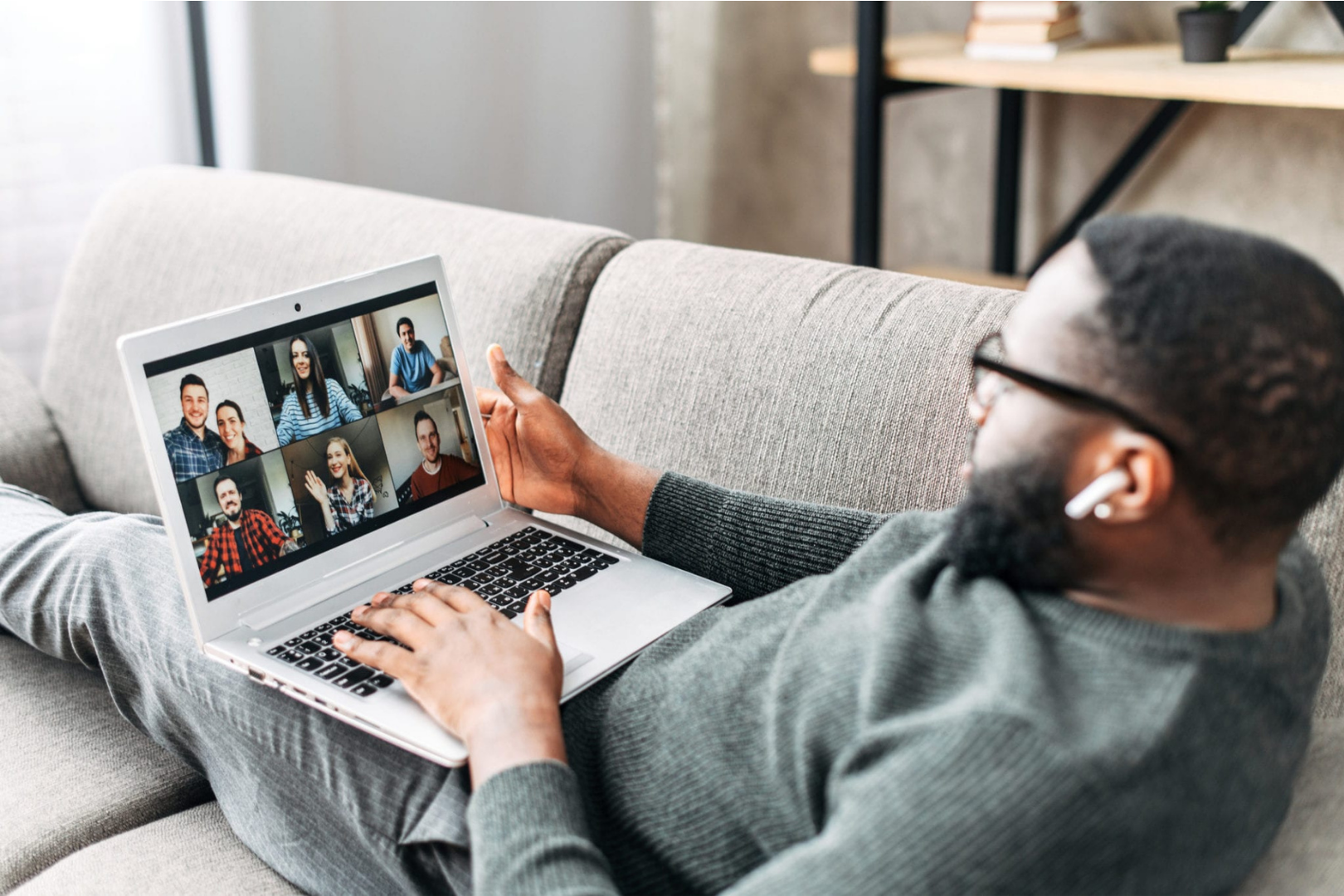 African American Man sitting on couch with laptop talking to other people virtually
